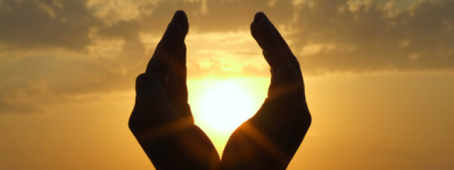 Picture of hands holding the sun at dawn